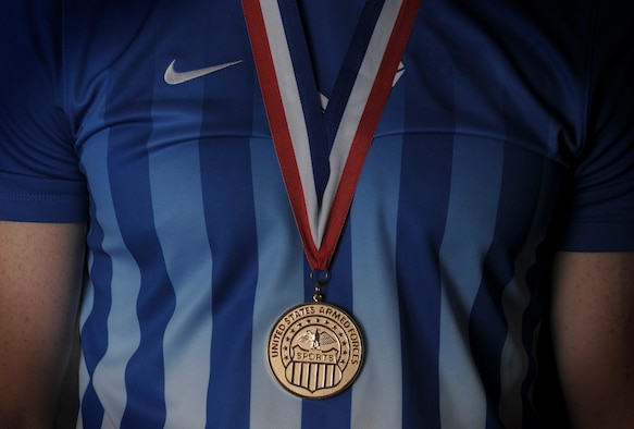 Airman 1st Class Timothy Bettes, 48th Force Support Squadron career development technician wears the Armed Forces Men's soccer championship medal, June 23, 2016 at Royal Air Force Lakenheath, England. The Air Force men's soccer team played the U.S. Navy for the championship, May 19, 2016 at Fort Benning, Georgia, winning 3-2. (U.S. Air Force photo/Senior Airman Dawn M. Weber)
