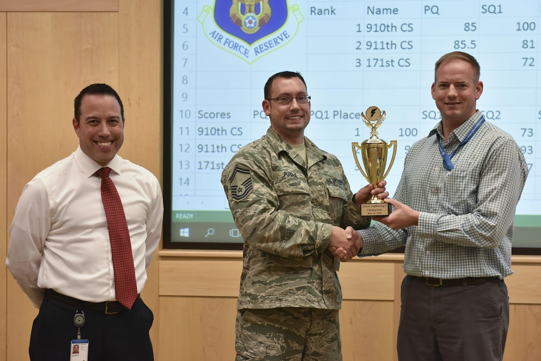Captain Geoffrey Dobson, cyber war gaming program manager at Carnegie Melon University and officer in charge of cyber assurance with the 911th Airlift Wing, and Master Sgt. Robert Beveridge, and software engineer at CMU and computer systems operator with the 910th Airlift Wing, present a trophy to Senior Master Sgt. Jamie Purola, cyber operations flight chief with the 910th Airlift Wing, at Carnegie Melon University, Pennsylvania, May 18, 2016. The 910th was the winner of the Cyber Lightning exercise held at CMU, where teams from the 911th AW, the 910th AW and the 171st Air Refueling Squadron competed to eliminate cyber threats in a training cyber environment. (U.S. Air Force photo by Airman Beth Kobily)