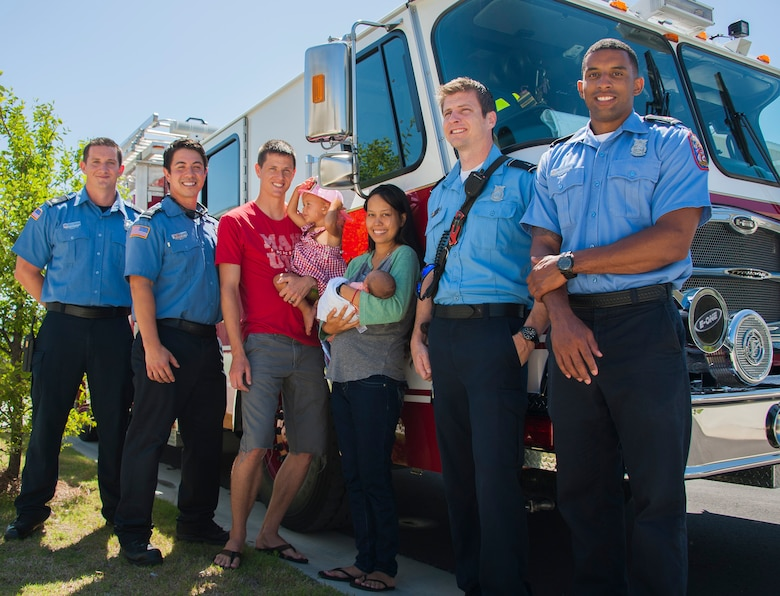 Kyle Vaughn, Timothy Panzer, Mark Merrill and Walter Carney, all 96th Civil Engineer Group firefighters, stand with Airman 1st Class Josiah Zimmerman, his wife, Leana, and their children during a visit June 20, 2016, at Eglin Air Force Base, Fla. The firefighters helped the Zimmermans deliver their baby boy, Luca, at their home on base after responding to a 911 call. (U.S. Air Force photo/Ilka Cole)