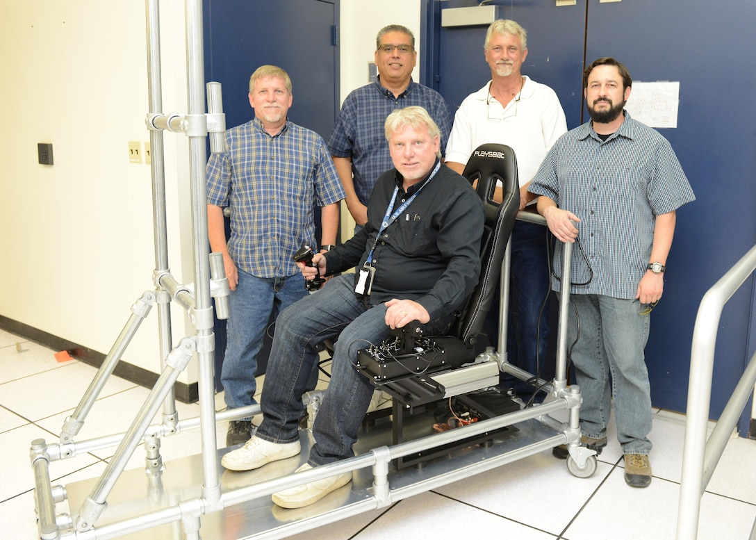 The Portable Manned Interactive Cockpit being built by members of the 772nd Test Squadron should be completed and ready for use by July 2016. The innovation team members are, from rear left to right, Curtis Westfall, Victor Cruz, Gary Johnson, Kevin Dolber and Orion Westfall, seated. (U.S. Air Force photo/Kenji Thuloweit)
