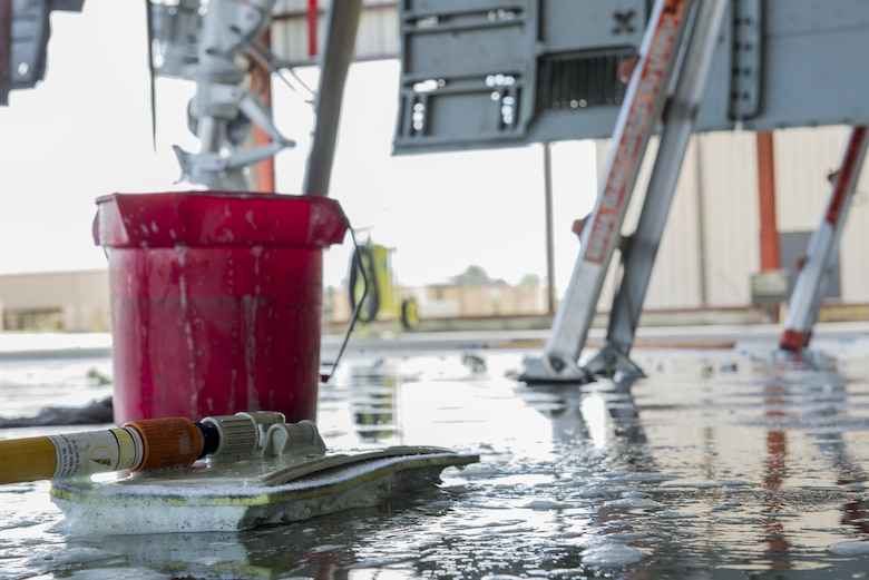 Aircraft washing materials rest on a wet floor during an A-10C Thunderbolt II wash, June 16, 2016, at Moody Air Force Base, Ga. Strong chemicals are used to clean the aircraft in order to eat away the residue weapons systems leave behind. (U.S. Air Force photo by Airman Daniel Snider/Released)