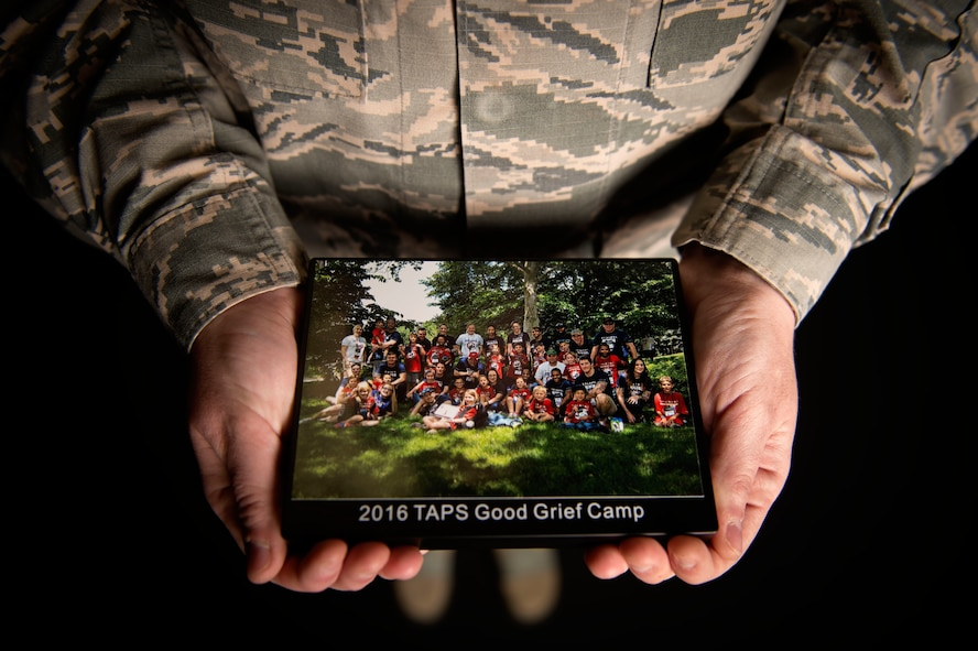 "Staff Sgt. Destini Yaden, a mental health specialist assigned to the 27th Special Operations Medical Operations Squadron, shows a photo of significance to her June 15, 2016, at Cannon Air Force Base, N.M. ""The significance of the photo is because the girl I mentored for nine years, was mentoring for her first time,"" said Yaden. ""Also I was able to be mentor to the son of one of my fallen friends.""(U.S. Air Force photo/Tech. Sgt. Manuel Martinez)"