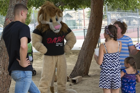 The Drug Abuse Resistance Education Lion, Daren, interacts with community members during the Joshua Tree Community Days Summer Splash at the Joshua Tree Community Center in Joshua Tree, California.
