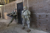 Army Spcs. John Nicastro, left, and Forrest Watkins prepare to breach a door during annual training at Camp Ethan Allen Training Site, Jericho, Vt., June 15, 2016. Nicastro and Watkins are assigned to the Vermont National Guard's Company A, 3rd Battalion, 172nd Infantry Regiment, 86th Infantry Brigade Combat Team. Air National Guard photo by Tech. Sgt. Sarah Mattison