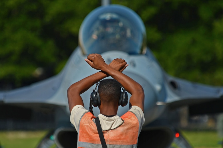 U.S. Air Force Airman 1st Class Cameron Crawford, 20th Aircraft Maintenance Squadron tactical aircraft maintainer, marshals an F-16CM Fighting Falcon for hot-pit refueling during a surge at Shaw Air Force Base, S.C., June 21, 2016. Throughout the surge, tactical aircraft maintainers marshalled over 30 aircraft a day. (U.S. Air Force photo by Airman 1st Class Christopher Maldonado)