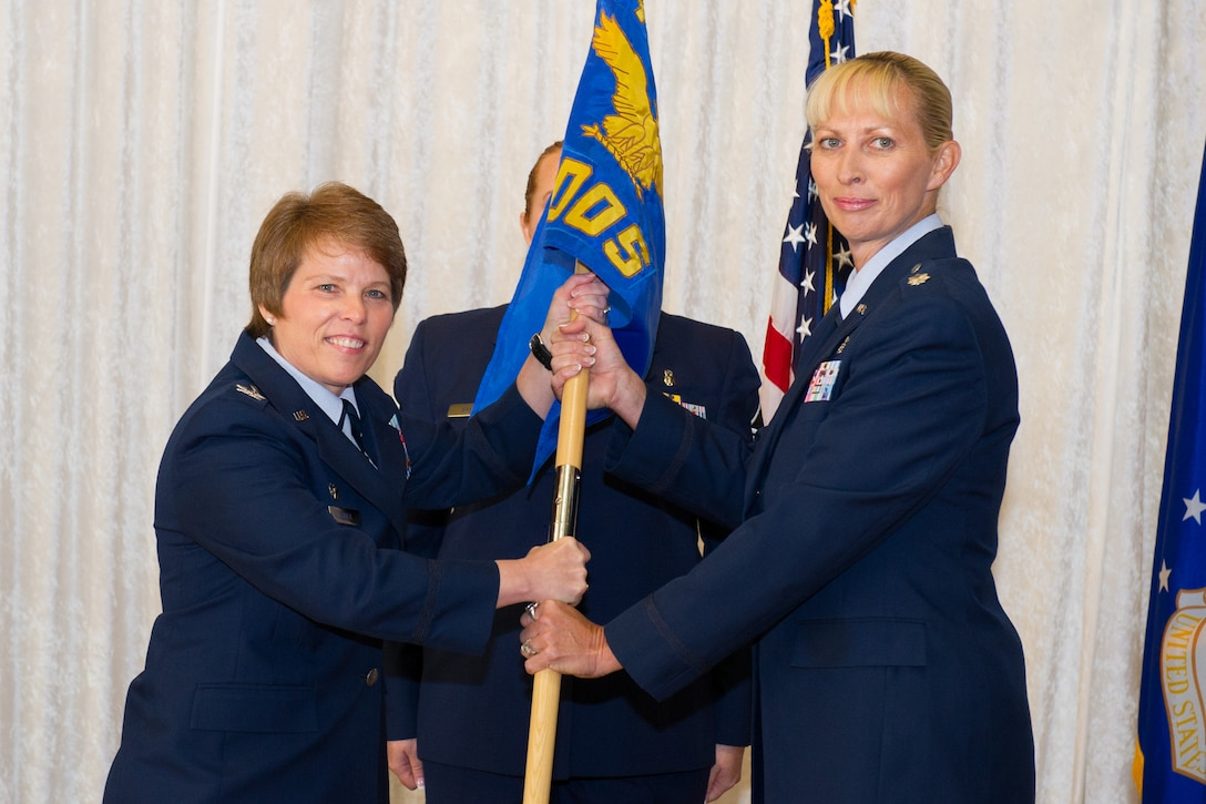 Col. Julie Stola, 45th Medical Group commander, presents Lt. Col. Donna Fox, 45th Medical Operations Squadron commander, with the guidon during a change of command ceremony June 24, 2016, at Patrick Air Force Base, Fla. Changes of command are a military tradition representing the transfer of responsibilities from the presiding official to the upcoming official. (U.S. Air Force photo/Matthew S. Jurgens/Released)