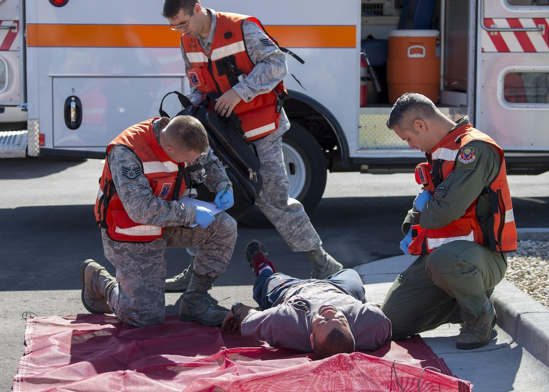 Military members tend to a simulated victim during an active shooter exercise June 23, 2016, in downtown Mountain Home, Idaho. The 366th Medical Group sent first responders to the city center to assist local emergency medical technicians during the active shooter exercise.(U.S. Air Force photo by Senior Airman Jeremy L. Mosier/Released)