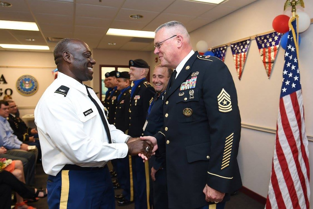 Col. D.D. Mayfield, left, commander of the Defense Contract Management Agency-Chicago, shakes hands with Sergeant Maj. James Rogers, G3/Operations Sergeant Major, after a change of command ceremony where Mayfield relinquished command to Col. Paul Mazure, June 23, 2016. Soldiers assigned to the 85th Support Command assisted with color guard support to DCMA. (Photo by Mr. Anthony L Taylor)