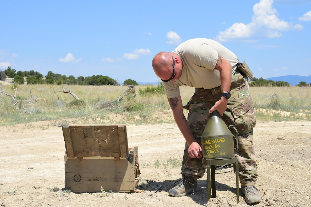 Staff Sgt. Robert Rich, 140th Explosive Ordnance Disposal operator, prepares a 40-pound shape charge to be detonated June 23, 2016, at the Airburst Range on Fort Carson, Colo. Many of the munitions the 140th EOD use are left over from decades of munitions manufacturing. The 40-pound shape charge was manufactured in April of 1953. (U.S. Air Force photo by Airman 1st Class Luke W. Nowakowski/Released)