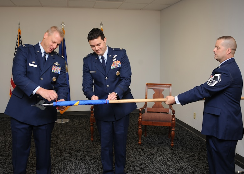 U.S. Air Force Col. Gregory Marzolf, 414th Combat Training Squadron, commander,  Lt. Col. Christopher Cunningham, Detachment 1, 414th CTS, commander and Senior Master Sgt. Stephen Hoss, 414th CTS, Red Flag superintendent, unroll the guidon of Detachment 1 at Davis-Monthan Air Force Base, Ariz., June 24, 2016. The new detachment will be planning, coordinating and executing Angel Thunder 2016. (U.S. Air Force photo by Airman 1st Class Ashley N. Steffen/ Released)