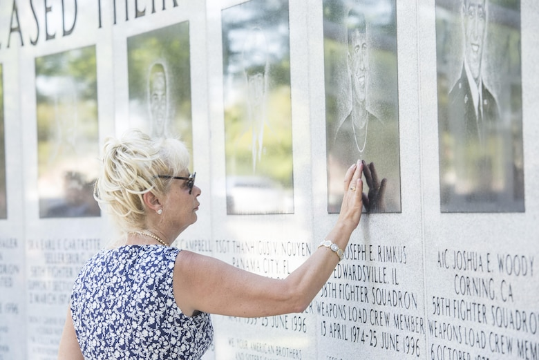 Dari Bradley, aunt of Airman 1st Class Joseph Rimkus, touches a portrait of him on the Khobar Towers Memorial wall June 24, 2016, after the a memorial ceremony at Eglin Air Force Base, Fla. Rimkus was a weapons load crewmember from the 58th Tactical Fighter Squadron who lost his life as a result of the Khobar Towers bombing June 25, 1996. (U.S. Air Force photo by Senior Airman Stormy Archer/Released)