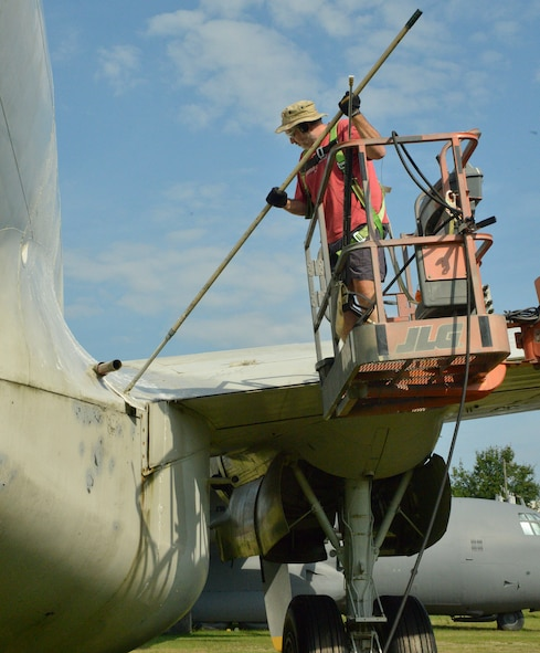 Erwin Ross, exhibit specialist, uses a scrub brush to get the grime off of a C-121 Constellation. (U.S. Air Force photo by Ed Aspera)