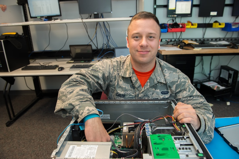 Airman Marc Galui, a 628th Communications Squadron client system technician, smiles while fixing a computer May 17, 2016 at Joint Base Charleston, S.C. Galui is looking forward to having his family from Detroit, Mich. visit him during the upcoming 4th of July weekend. Independence Day makes him feel proud to serve and is a time to reflect on the price of freedom. (U.S. Air Force photo/Staff Sgt. Jared Trimarchi)