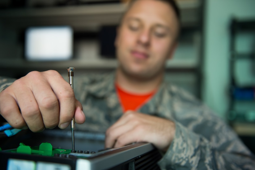 Airman Marc Galui, a 628th Communications Squadron client system technician, tightens a screw on a computer May 17, 2016 at Joint Base Charleston, S.C. Galui is looking forward to having his family from Detroit, Mich. visit him during the upcoming 4th of July weekend. Independence Day makes him feel proud to serve and is a time to reflect on the price of freedom. (U.S. Air Force photo/Staff Sgt. Jared Trimarchi)