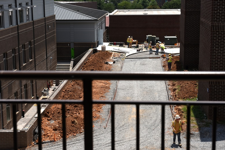 Workers build forms and pour a concrete sidewalk leading from the billeting office to Spruance Hall (in the background) June 13, 2016, among other interior and exterior projects on the new facility at the I.G. Brown Training and Education Center in Louisville, Tenn. (U.S. Air National Guard photo by Master Sgt. Mike R. Smith/Released)