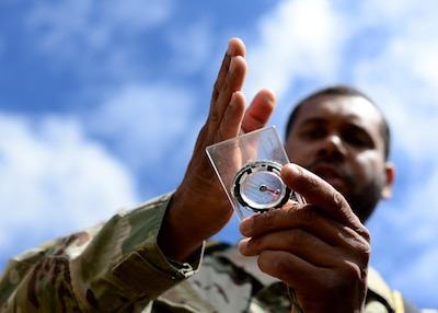U.S. Air Force Tech. Sgt. Johnie Tucker, 818th Mobility Support Advisory Squadron survival evasion resistance and escape specialist air advisor, demonstrates navigation skills for Kenyan Defense Force members at Laikipia Air Base, Kenya, June 23, 2016. More than 50 U.S. Air Force Airmen participated in the first African Partnership Flight in Kenya. The APF is designed for U.S. and African partner nations to work together in a learning environment to help build expertise and professional knowledge and skills in key areas such as personnel recovery command and control, survival and evasion principles and tactical combat casualty care. (U.S. Air Force photo by Tech. Sgt. Evelyn Chavez/Released)