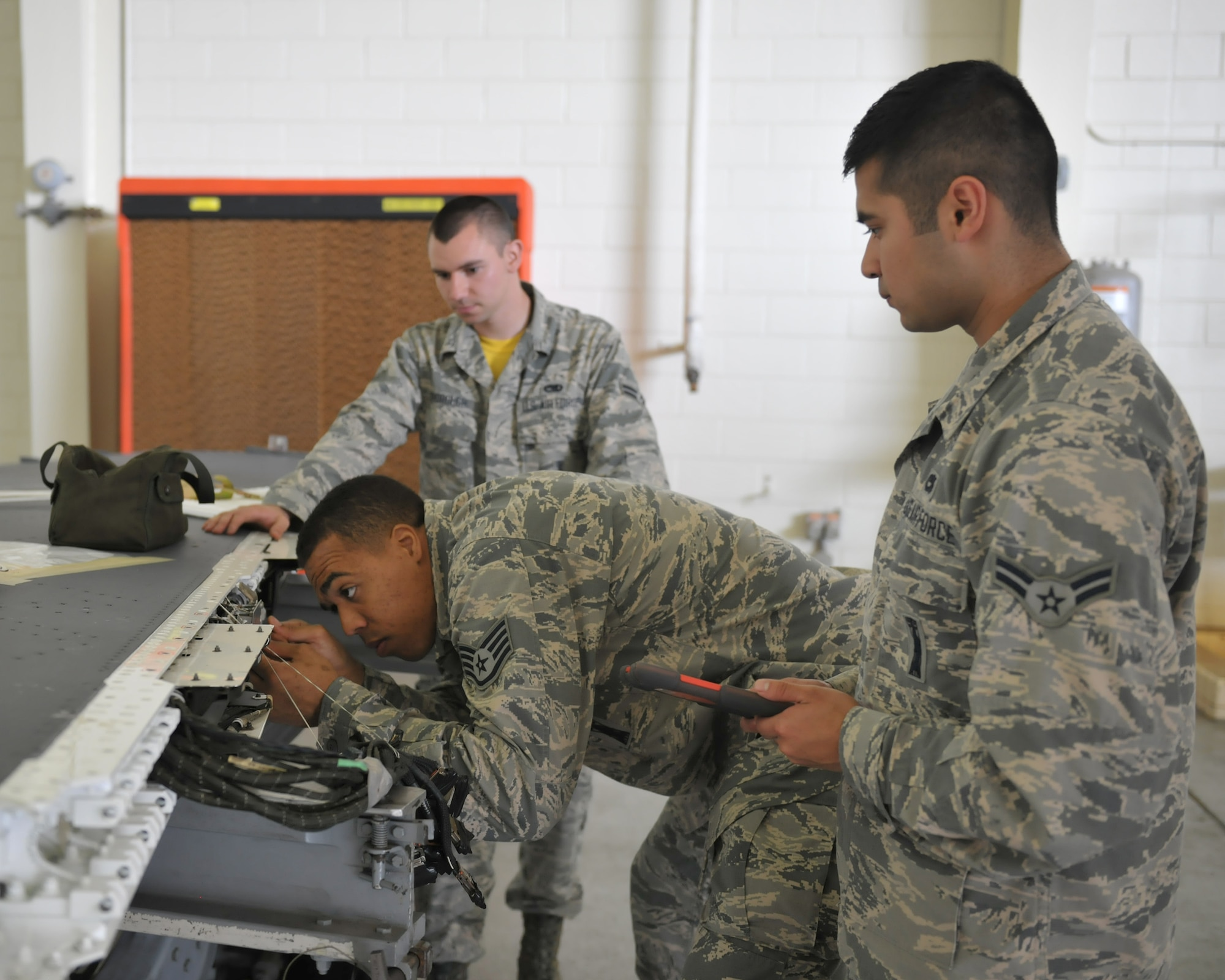 Staff Sgt. Dwight Hunter, 8th Aircraft Maintenance Squadron Aircraft Armament Systems team chief, verifies connectors for a protective covering and proper routing of wires inside a wing as team members observe June 24, 2016 at Kunsan Air Base, Republic of Korea. Hunter and his team are working with other maintenance Air Force Specialty Codes on a simultaneous double wing replacement. (U.S. Air Force photo/Master Sgt. David Miller)