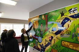 Lauren Freed, Cape Cod Learners Cooperative, examines the mural that her students painted and donated to the New England District on May 1, 2016.
