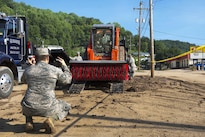 An airman directs a team member operating a street sweeper to unload from a truck in Clendenin, W.Va., June 26, 2016, while assisting with the response to severe flooding in the area. The airmen are assigned to the West Virginia Air National Guard. Air National Guard photo by Tech. Sgt. De-Juan Haley