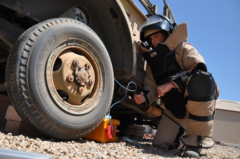 Senior Airman Logan Avery, 56th Civil Engineer Squadron Explosive Ordnance Disposal team leader, renders safe a simulated homemade explosive June 24 at Luke Air Force Base. Avery is wearing an EOD 9 Bomb Suit and Helmet for