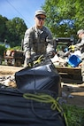 Air Force Tech. Sgt. Brian Grim picks up debris in Clendenin, W.Va., June 26, 2016, while assisting with flood response efforts. Grim is assigned to the West Virginia Air National Guard's 167th Airlift Wing. Air National Guard photo by Tech. Sgt. De-Juan Haley