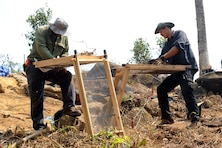 Joe Griffin (left), senior archeologist for the U.S. Army Corps of Engineers, and Petty Officer 2nd Class Cody Wilcoxson use mobile screening stations to examine excavated dirt in the Xiangkhoang Province, Lao People's Democratic Republic on Mar. 19, 2016. Members of the Defense POW/MIA Accounting Agency deployed to the area in hopes of recovering the remains of a pilot unaccounted for since the Vietnam War era. (DoD photo by Staff Sgt. Jocelyn Ford, USAF/RELEASED)