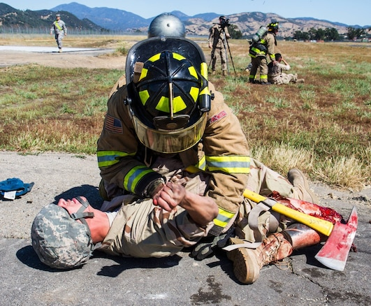 A U.S. Army firefighting Soldier participating in the WAREX training exercises hosted by 91st Training Division aids the victim of a downed helicopter scenario (simulated) on Fort Hunter Liggett, Calif. on May 9, 2016. Fire response Soldiers put out a fire in the training helicopter as other firefighters treat the casualties as part of a joint response operation.(U.S. Army photos by 1LT Kevin Braafladt 91st Training Division Public Affairs/Released)  #91TD2016WAREX