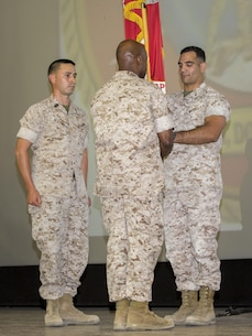 Lt. Col. Speros C. Koumparakis, outgoing commanding officer, passes the Communication Training Battalion's colors to Lt. Col. Barian A. Woodward, oncoming commanding officer, during the battalion's change of command ceremony at Sunset Cinema aboard the Marine Corps Air Ground Combat Center, Twentynine Palms, Calif., June 21, 2016. (Official Marine Corps photo by Lance Cpl. Levi Schultz/Released)