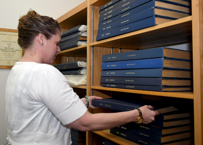 Shawn Riem, 30th Space Wing historian, retrieves historical documentation June 16, 2016, Vandenberg Air Force Base, Calif. Riem encourages all units to send her any mission documentation. This will allow her to assimilate pertinent information into her archives, as opposed to it being lost in the sands of time. (U.S. Air Force photo by Senior Airman Kyla Gifford/Released)