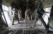 Paratroopers, with the U.S. Army's 82nd Airborne Division, prepare to jump from a C-130 Hercules while Gabonese Defense Forces jumpmasters assist them with exiting the aircraft during exercise Central Accord 2016 in Libreville, Gabon, June 22, 2016. The U.S. Army Africa exercise is an annual, combined, joint military exercise that brings together partner nations to practice and demonstrate proficiency in conducting peacekeeping operations. (DOD photo/Tech. Sgt. Brian Kimball)