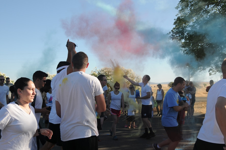 Tech Sgt. Randy, from the 9th Intelligence Squadron, throws colored powder at runners during the start of the 5K color run at Beale Air Force Base, June 24, 2016. This year Beale was able to celebrate the LGBT community as DoD has officially made June LGBT Pride Month. (U.S. Air Force photo by Airman 1st Class Jessica B. Nelson)