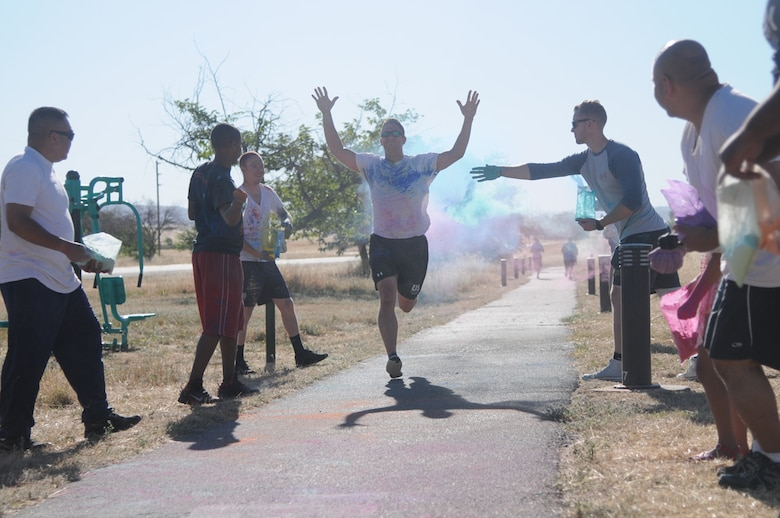 Master Sgt. Daniel, from the 548th Operations Support Squadron, gets doused with colored powder while finishing the annual 5K color run at Beale Air Force Base, June 24, 2016. This year Beale was able to celebrate the LGBT community as DoD has officially made June LGBT Pride Month. (U.S. Air Force photo by Airman 1st Class Jessica B. Nelson)