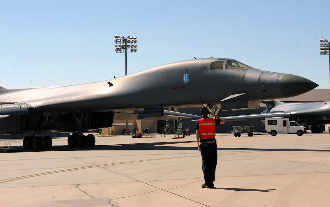 An Airman from the 37th Aircraft Maintenance Unit marshals a B-1 bomber out to the flightline at Ellsworth Air Force Base, S.D., to perform a flyover in honor of U.S. Army Air Corps Staff Sgt. David Thatcher, June 27, 2016. Thatcher, one of the last remaining Doolittle Raiders, passed away from complications of a stroke on June 22. (U.S. Air Force photo by Airman 1st Class Denise M. Nevins/Released)