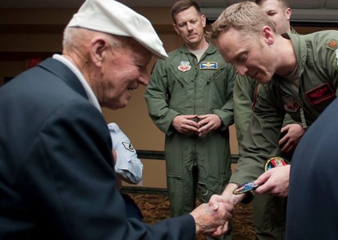 U.S. Army Air Corps Staff Sgt. David Thatcher, left, receives a recent B-1 bomber deployment patch during the Final Doolittle Raider Toast in November 2013. Following the Doolittle Raid, Thatcher served in England and Africa until January 1944, flying in a B-26 bomber in 26 missions over North Africa and Europe, including the first bombing raid over Rome. (Courtesy photo/Released)