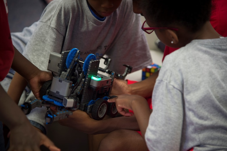 Children play with a model robot during the opening of the Center of Innovation at the Joint Base Andrews Youth Center, here, June 24, 2016. The center's goal is to excite children about science, technology, engineering, and math, also known as STEM subjects. (U.S. Air Force photo by Senior Airman Mariah Haddenham)