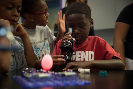 A child looks through a microscope during the opening of the Center of Innovation at the Joint Base Andrews Youth Center, here, June 24, 2016. The center is one of 20 like it around the world, allowing children from military families the chance to get interested in science, technology, engineering, and math subjects. (U.S. Air Force photo by Senior Airman Mariah Haddenham)
