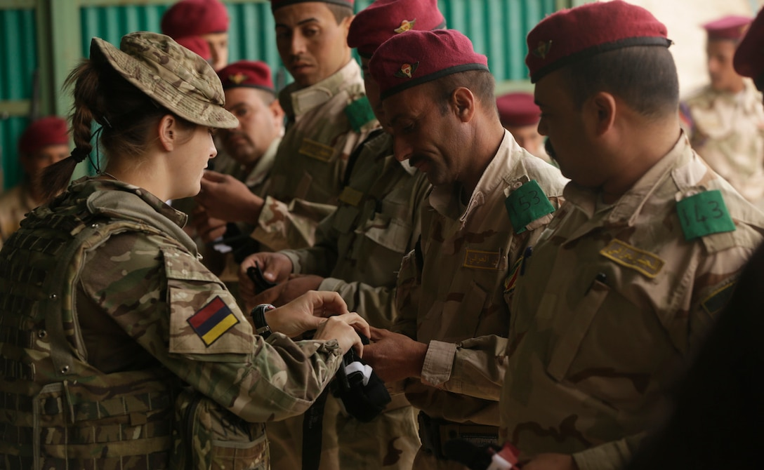 A British soldier with the Royal Army Medical Corps helps an Iraqi soldier enrolled in the Junior Leaders Course (JLC) prepare a tourniquet during a skills evaluation at Camp Taji, Iraq, earlier this year. (U.S. Army photo by Sgt. Paul Sale)