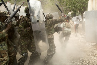 Service members from several partner nations fend off role players acting as rioting villagers as part of crowd control training during Tradewinds 2016 at Twickenham Park Gallery Range, Jamaica, June 25, 2016. Tradewinds is a Carribbean-focused multinational training exercise with maritime and land phases aimed at improving security and disaster relief assistance. Marine Corps photo by Cpl. Justin T. Updegraff