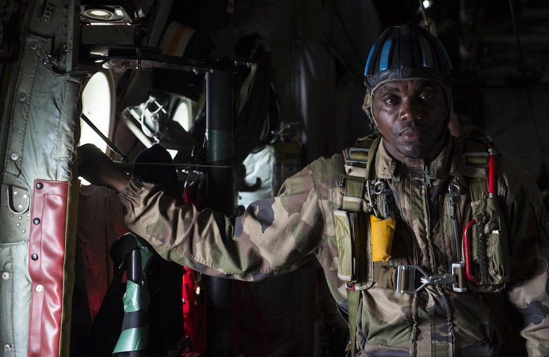 Chief Warrant Officer 2nd Class Lawangu, a jumpmaster with the Gabonese armed forces, assists with directing airdrops for paratroopers from the U.S. Army's 82nd Airborne Division during exercise Central Accord 2016 in Libreville, Gabon, June 22, 2016. The U.S. Army Africa exercise is an annual, combined, joint military exercise that brings together partner nations to practice and demonstrate proficiency in conducting peacekeeping operations. (DOD photo/Tech. Sgt. Brian Kimball)