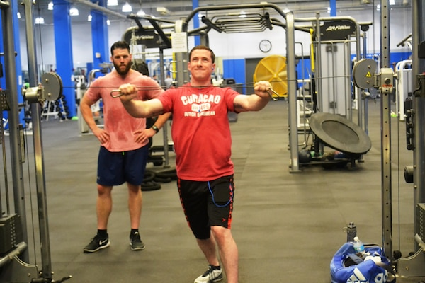 Matthew Eckenrode, left, looks on as Ryan Guarnere utilizes one on the machines in at the NSA-Philadelphia gym June 23. Both began working out together just a few weeks ago; however, Guarnere says with Eckenrode's assistance and motivation, he is already seeing results.