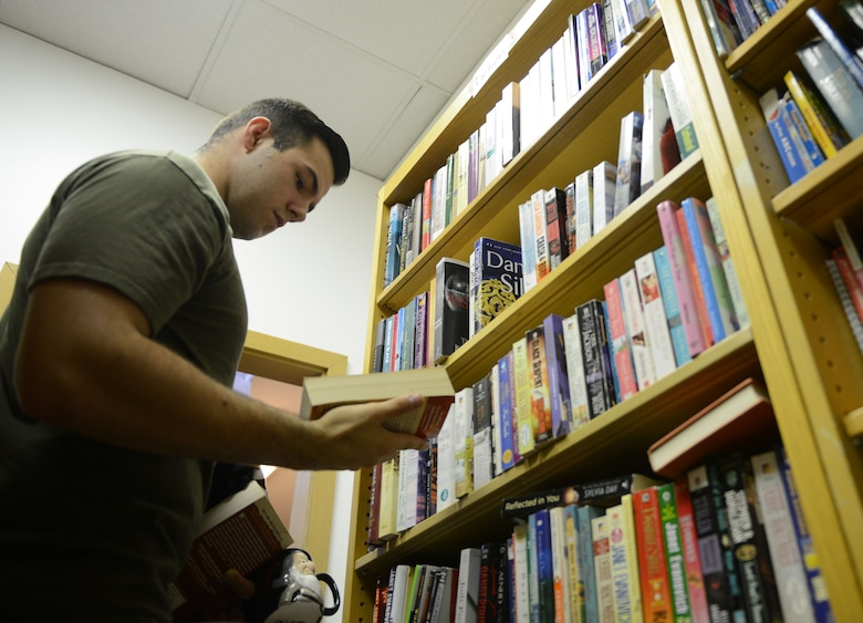 Airman 1st Class Jacob Fraas, 721st Aircraft Maintenance Squadron crew chief, looks at books being given away at the Airman's Attic at Ramstein Air Base, Germany, June 24, 2016. The Airman's Attic offers a wide range of household goods, clothing, electronics and toys to active duty military members E-5 and below. (U.S. Air Force Photo/ Airman 1st Class Joshua Magbanua)