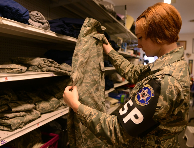 Airman Claire Hilborn, 569th U.S. Forces Police Squadron security forces member, looks at a pair of Airman Battle Uniform trousers at the Airman's Attic at Ramstein Air Base, Germany, June 24, 2016. The Airman's Attic offers free uniforms along with household goods to active-duty military members E-5 and below. (U.S. Air Force Photo/ Airman 1st Class Joshua Magbanua)