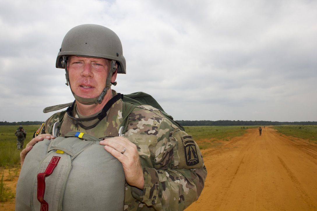 """Maj. Christopher Murphy, Commander of the 982nd Combat Camera Company, walks off St. Mere Eglise drop zone after a successful jump at Fort Bragg, N.C. on June 25, 2016. The 982nd, an Army Reserve unit, provides our military leaders and government officials first-hand, still and video imagery (both released and classified), of our forces in the field. They are the """"Eyes and Ears"""" of the decision makers.  (U.S. Army photo by Staff Sgt. Felix Fimbres)"""
