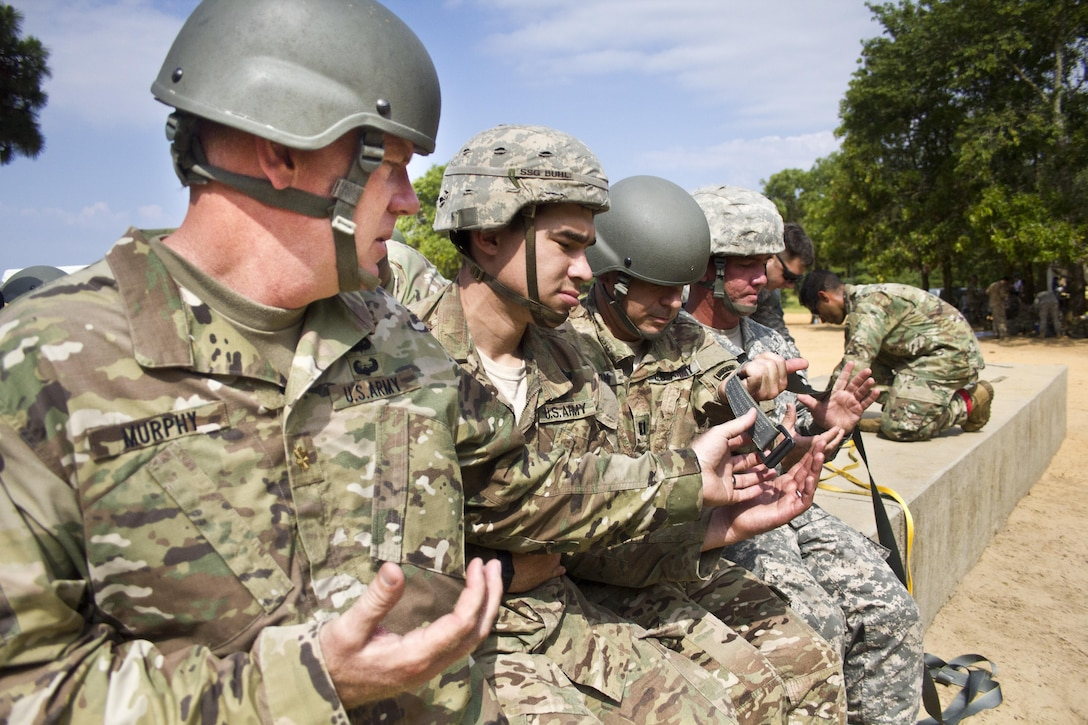 Maj. Christopher Murphy, Commander of the 982nd Combat Camera Company, and paratroopers from the U.S. Army Civil Affairs & Psychological Operations Command (Airborne), practice actions in the aircraft prior to an airborne operation over St. Mere Eglise drop zone near Fort Bragg, N.C. on June 25, 2016. The United States Army Civil Affairs & Psychological Operations Command (Airborne), an Army Reserve unit, conducts airborne operations in order to maintain currency and proficiency. USACAPOC(A) supports the Army and Joint Force with strategic, operational, and tactical civil affairs, military information support, and information operations capabilities across the range of military operations. (U.S. Army photo by Staff Sgt. Felix Fimbres)