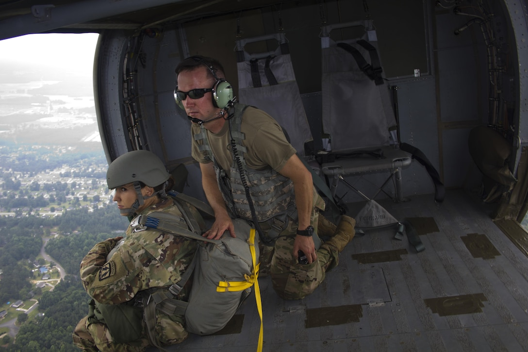 Spc. Kristen Root, 982nd Combat Camera Company, awaits the command to jump from Sgt. Christopher Emmons, U.S. Army Civil Affairs & Psychological Operations Command (Airborne), shouts commands inside a UH-60 Blackhawk during an airborne operation over St. Mere Eglise drop zone near Fort Bragg, N.C. on June 25, 2016. The USACAPOC(A), an Army Reserve unit, conducts airborne operations in order to maintain currency and proficiency. USACAPOC(A) supports the Army and Joint Force with strategic, operational, and tactical civil affairs, military information support, and information operations capabilities across the range of military operations. (U.S. Army photo by Staff Sgt. Felix Fimbres)