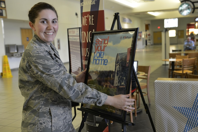 Air Force 2nd Lt. Kelly Lefler, unit voting assistance officer with the 673d Force Support Squadron, sets up a voting-assistance table at Joint Base Elmendorf-Richardson, Alaska, June 27, 2016. As a unit voting assistant officer, Lefler helps unit members with voting and filling out the correct forms. (U.S. Air Force photo by Airman 1st Class Valerie Monroy)