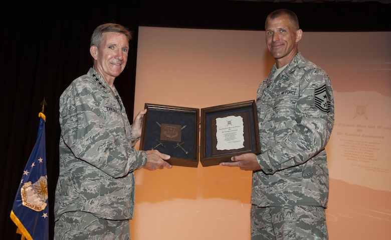 """Gen. Hawk Carlisle, commander of Air Combat Command, is presented with an invitation to be inducted into the Order of the Sword by Chief Master Sgt. Steve K. McDonald, ACC command chief, during an enlisted all-call at Joint Base Langley Eustis, June 28, 2016. When accepting the invitation, an emotional Carlisle told the mostly enlisted audience """"You have all made my life more than any man deserves."""" The Order of the Sword is the highest honor Air Force enlisted Airmen can bestow upon a commissioned officer who has made significant contributions to the enlisted force. (U.S. Air Force photo by Staff Sgt. Nick Wilson/Released)"""