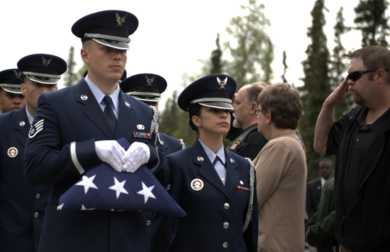"The Joint Base Elmendorf-Richardson Honor Guard carries a folded American flag into the funeral ceremony for Fred ""Bulldog"" Becker IV June 24. Bulldog was heavily involved in the Anchorage community, and more than 1,000 Airmen and Soldiers lined the streets for his processional, consisting of hundreds of motorcyclists from around the community. (U.S. Air Force photo by Senior Airman Kyle Johnson)"