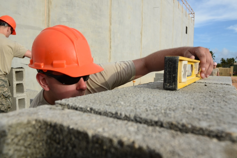 U.S. Air Force Senior Airman Ben Raymond, with the 157th Civil Engineering Squadron, New Hampshire Air National Guard, check the level of a cinder block while building a wall as part of the Commando Warrior Field Training Facility, Andersen Air Force Base, Guam, June 20, 2016. 157 CES Airmen are deployed to Guam for annual training where they are working on a construction project for the Pacific Command Regional Training Center.(Air National Guard photo by Airman 1st Class Ashlyn J. Correia)