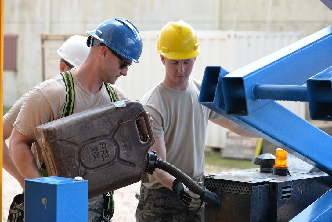 From the left, New Hampshire Air National Guardsmen Tech. Sgt. Ben Kipp and Senior Airman Benjamin Keeler fill up a scissor lift vehicle, Andersen Air Force Base, June 21, 2016. The 157 CES Airmen are deployed to Guam for annual training where they are working on the Commando Warrior Field Training facility, part of an ongoing construction project at the Pacific Command Regional Training Center. (Air National Guard photo by Tech. Sgt. Aaron Vezeau)